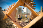 A view through a diamond-shaped wooden structure UB students built at Silo City. Students are visible in the middle of the photo, and a large grain elevator can be seen in the background.
