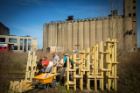 In the foreground are students working on their structure, with a tall grain elevator visible in the background.