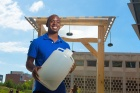 Deshawn Henry, holding a large plastic jug of water, stands in front of a 6-foot-tall water lens that uses sunlight to purify water.