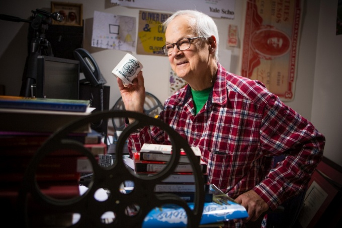 Tony Conrad, wearing a red plaid shirt with a green t-shirt underneath, holding a coffee cup while sitting in his office.