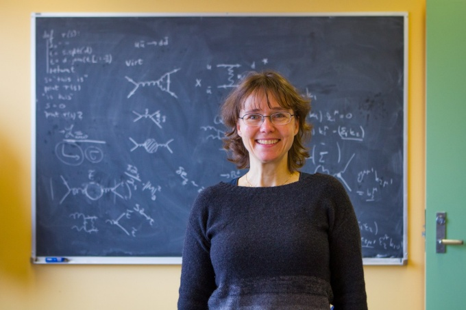 Doreen Wackeroth, UB professor of physics, stands in front of a blackboard.