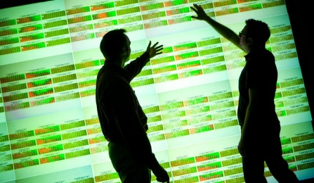 Two silhouetted people pointing at a lit-up screen showing scientific research.