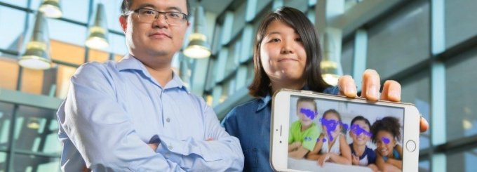From left to right, Wenyao Xu, University at Buffalo assistant professor of computer science and engineering, and undergraduate Kun Woo Cho, show a smartphone with the autism tracking software they are developing. The purple blotches show where a child looks. This photo indicates no autism spectrum disorder. Credit: Douglas Levere.