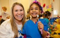A student volunteer smiles with a young child holding a toothbrush.