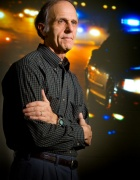 environmental portrait of UB researcher John Violanti standing, arms crossed, next to a police cruiser at night.