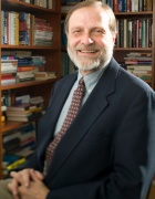 portrait of Lynn Kozlowski in front of a book case in his office.