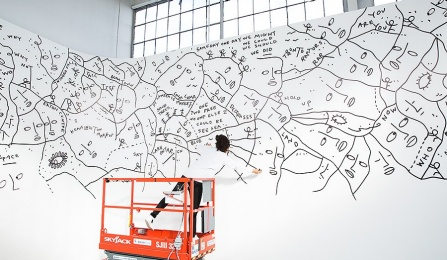 Shantell Martin uses a high-lift to work on a mural.