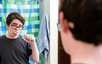 Bored looking teenage boy brushing his teeth