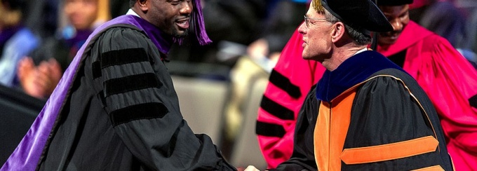 A professor shakes a law school student's hand at graduation.