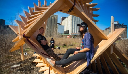 UB students sitting inside a wooden structure they made at Silo City in Buffalo.