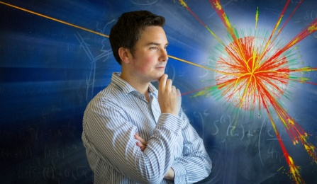 Ciaran Williams stand in front of blackboard with image of particle exploding.