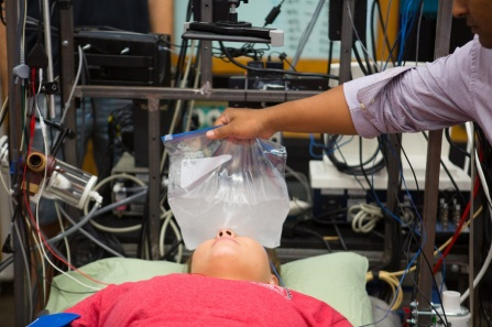 Researcher places a plastic baggy of ice water over a study participant's forehead, eyes and cheeks.