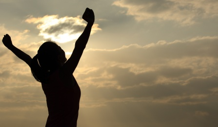 a woman raises her arms up in victory in the sunlight.
