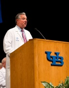 Michael Cain, MD, in white coat at podium