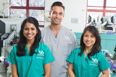 Three students in grey or green scrubs smiling in dental clinic.