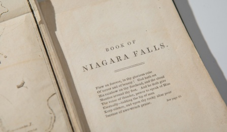 A book is opened to the inside page titled, 'A Book of Niagara Falls.'
