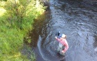 A scientist wading in a stream.