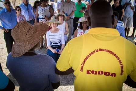 SUNY Chancellor Kristina Johnson (wearing hat and striped shirt) listens to a presentation during a recent visit to Arcahaie, Haiti, site of the proposed sustainable village and learning community.