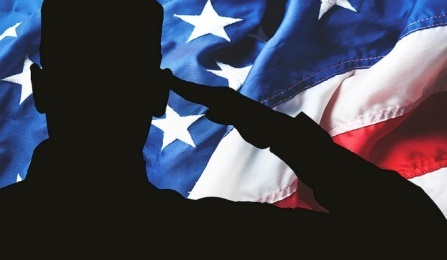 Silhouette of soldier saluting U.S. flag.