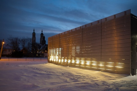 Nighttime photo depicting a new facade designed by UB architect Christopher Romano, in which the building glows with light.