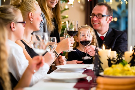 parents and children sit at a holiday table with wine glasses.