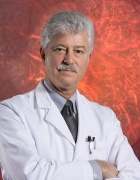 Steven Fliesler standing in white coat with image of eye in background