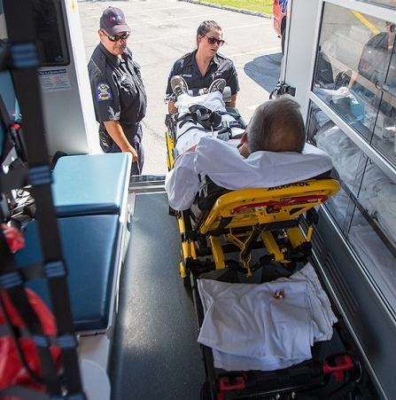 Photo of a man in a gurney being taken out of an ambulance.