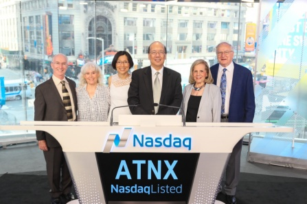 "A group of people standing at a podium that reads ""Nasdaq"", with the letters ATNX displayed on the front."