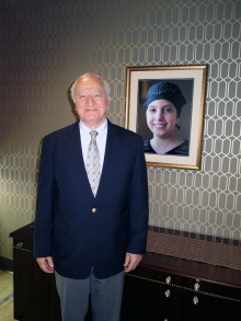 Allen Barnett wearing a suit and standing in front of a portrait of his granddaughter, Carly.