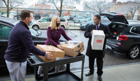 L to R Michael O'Hara and Heather Mattiuzzi of the Buffalo City Mission receive boxes from Praveen Arany.