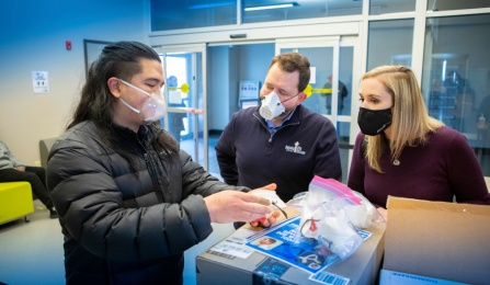 L to R: UB dental student Philip Sales shows the clear, reusable face mask produced by UB to Michael O'Hara and Heather Mattiuzzo of the Buffalo City Mission.