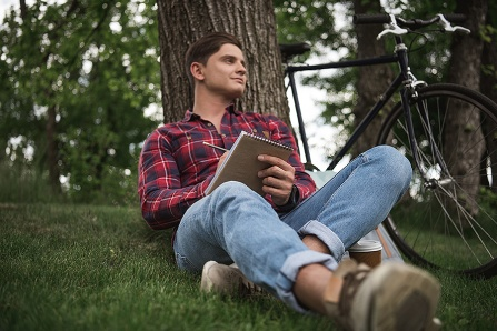 A young man sits in front of a tree with a writing pad in his hand and a bicycle in the background.