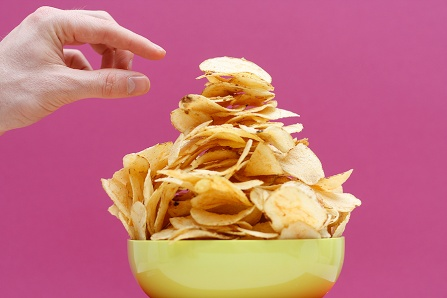 A large bowl of potato chips with a hand reaching to take a chip.