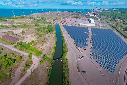 Drone photograph of the Steel Sun and Steel Wind Lackawanna, NY site featuring solar panels and wind turbines on the shores of Lake Erie.