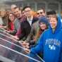 UB students line up and place their hands on a solar panel