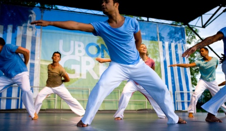 Two male dancers in blue gesture on stage at a UB on the Green outdoor event.
