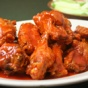 Photo of a plate of saucy chicken wings.